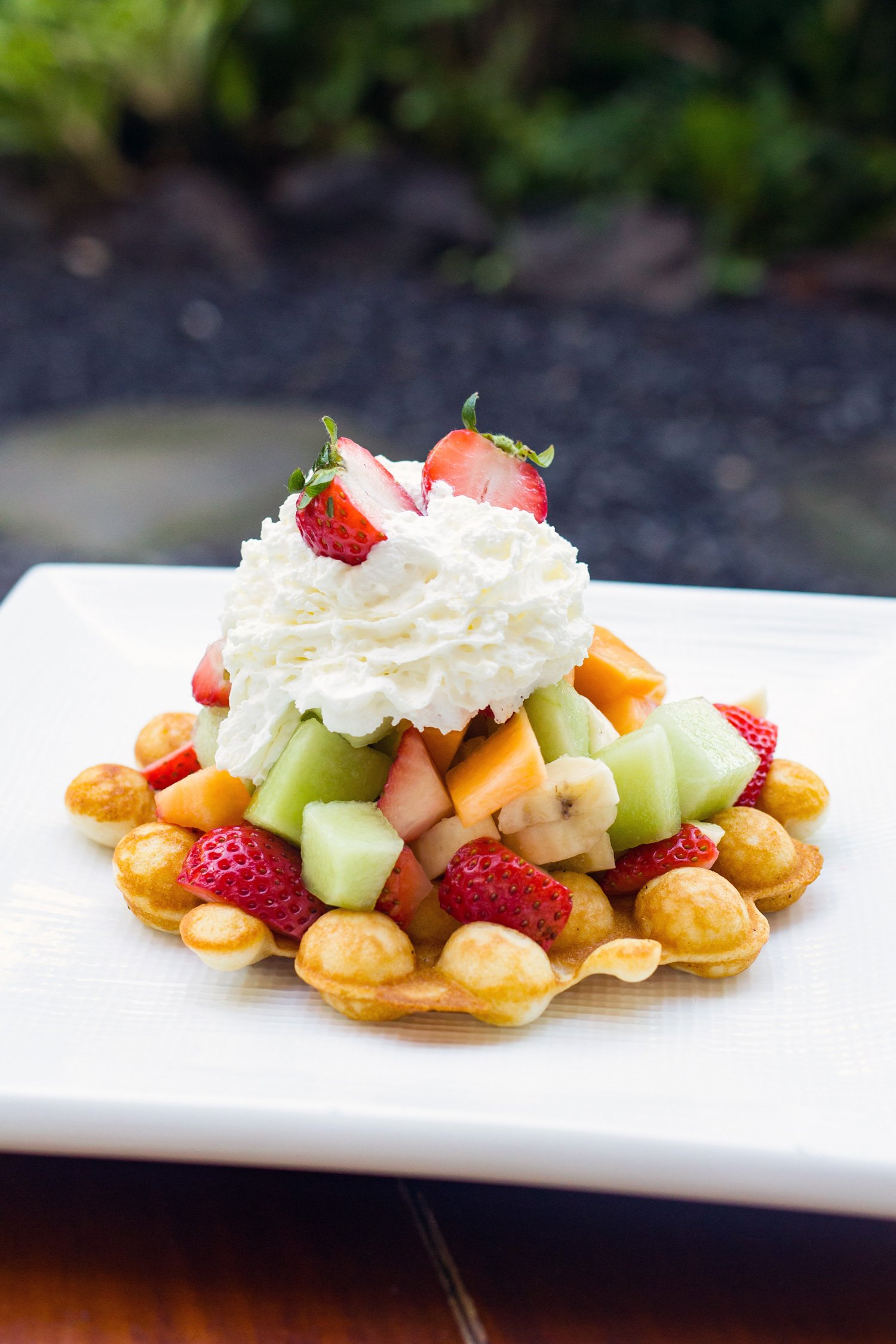 A Belgian Puffle with whipped cream and fruit