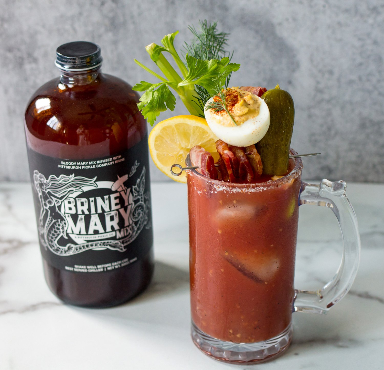 Pittsburgh Pickle Briney Mary Mix and A Bloody Mary With A Deviled Egg, Bacon and Pickle On Top.