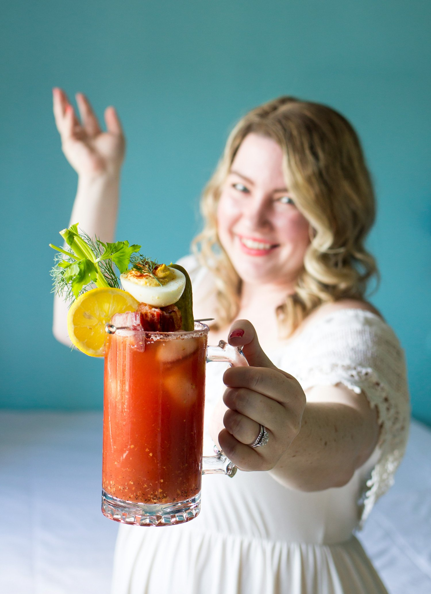 Natasha smiling will holding a giant Briney Mary in a Beer Mug