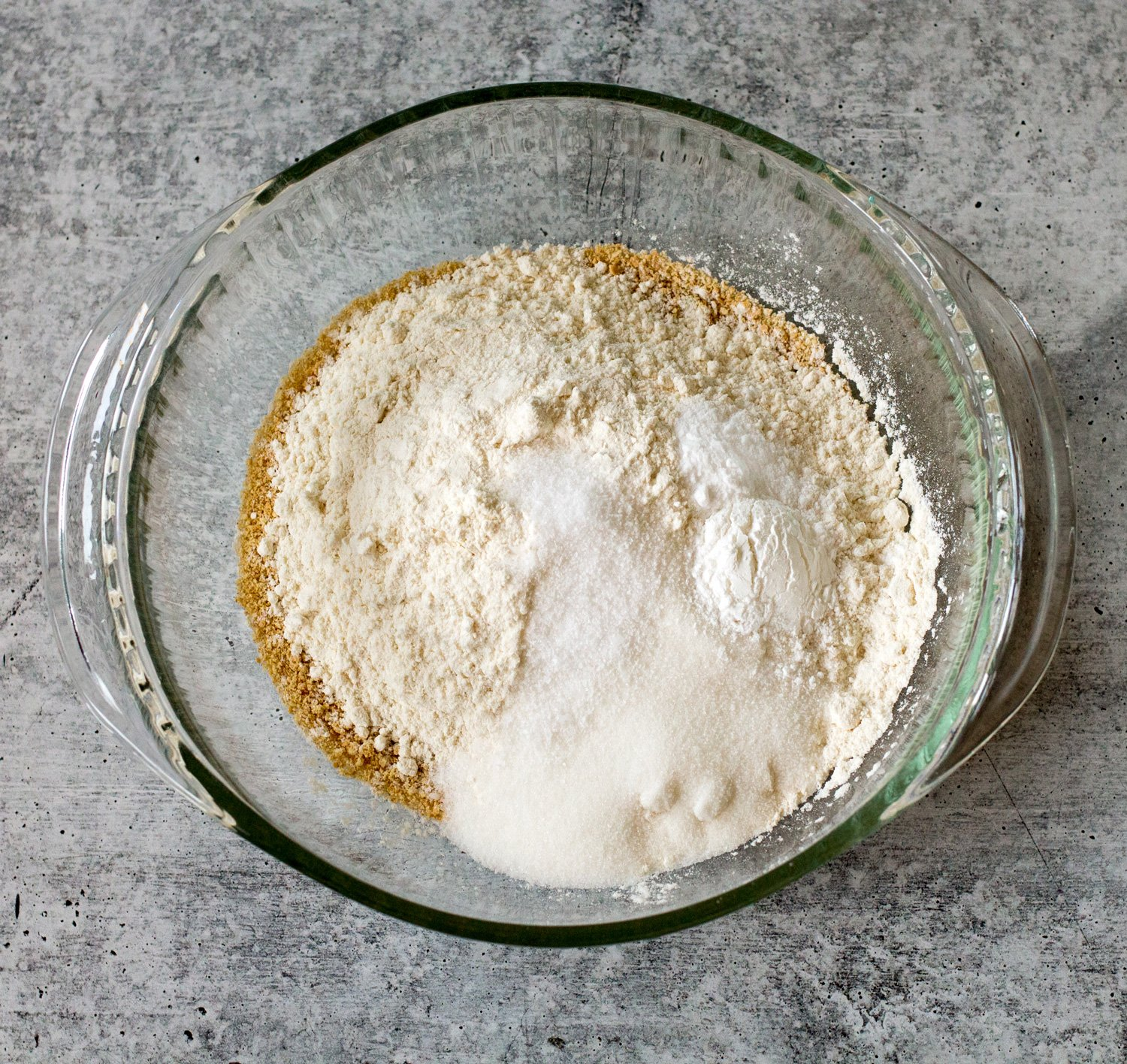 Crushed Graham Crackers, Flour and other pancake ingredients in a mixing bowl.