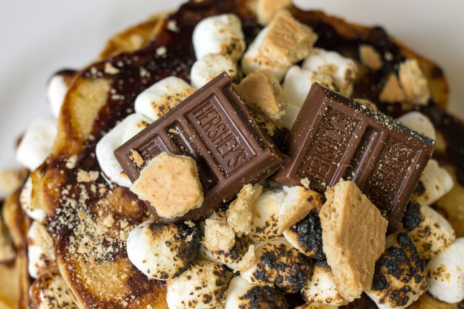 Up close photo of roasted marshmallows, chocolate bar, and graham cracker pieces on top of the pancakes.