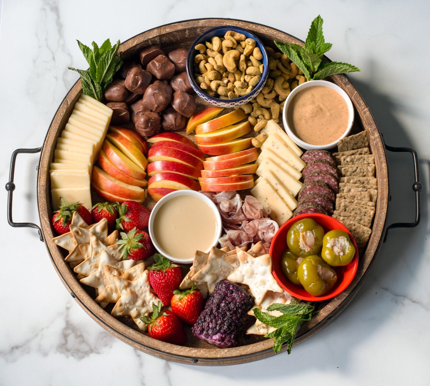 A Sweet And Savory Cheeseboard on A Large Round Tray