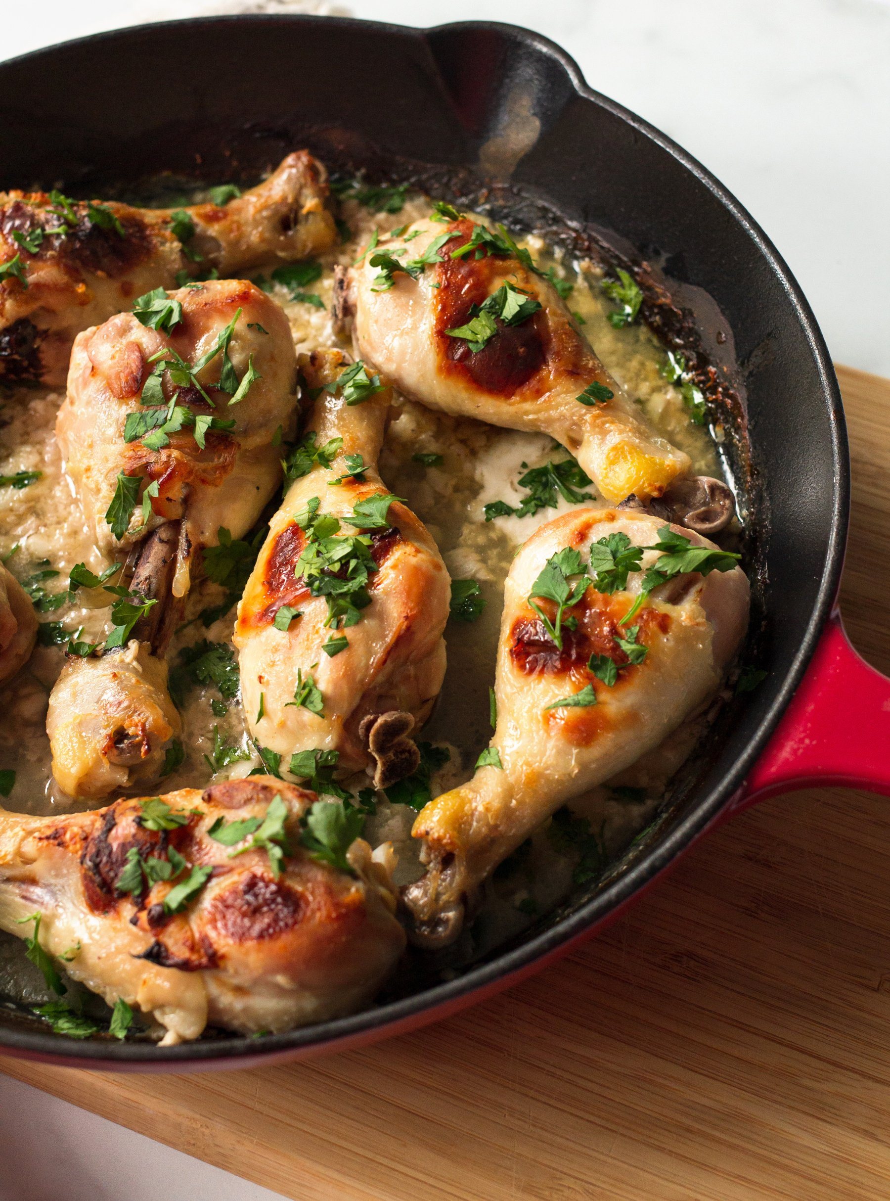Large Chicken Drumsticks in a Red Cast Iron Skillet Sprinkled With Parsley