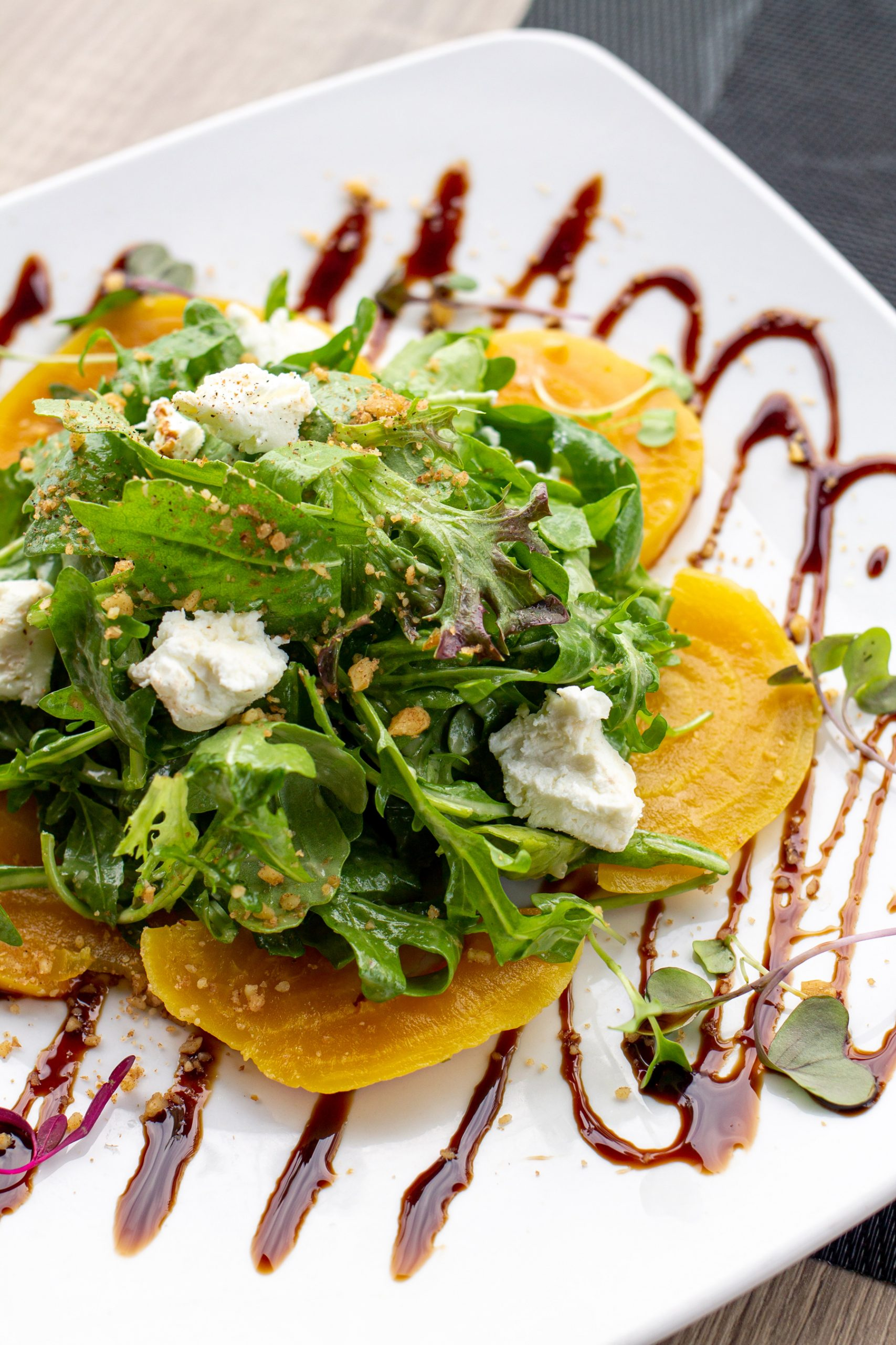 Golden Beets, Arugula and Goat Cheese on a large white plate.
