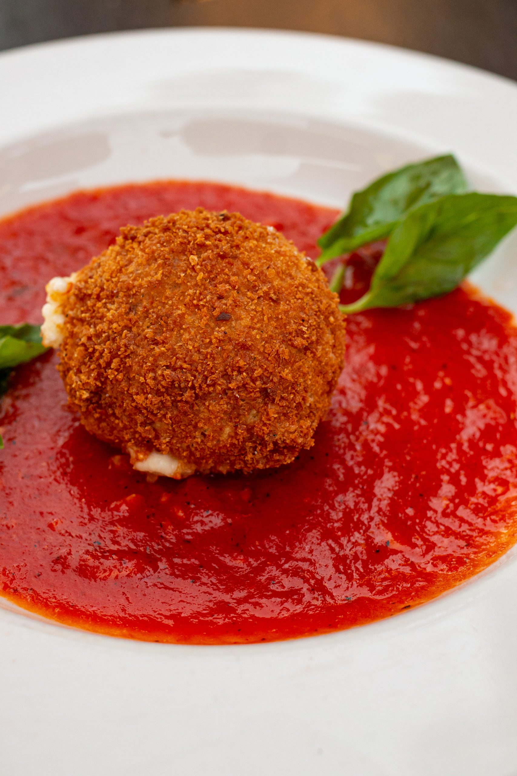 Fried Burrata Cheese in a shallow bowl of marinara sauce.