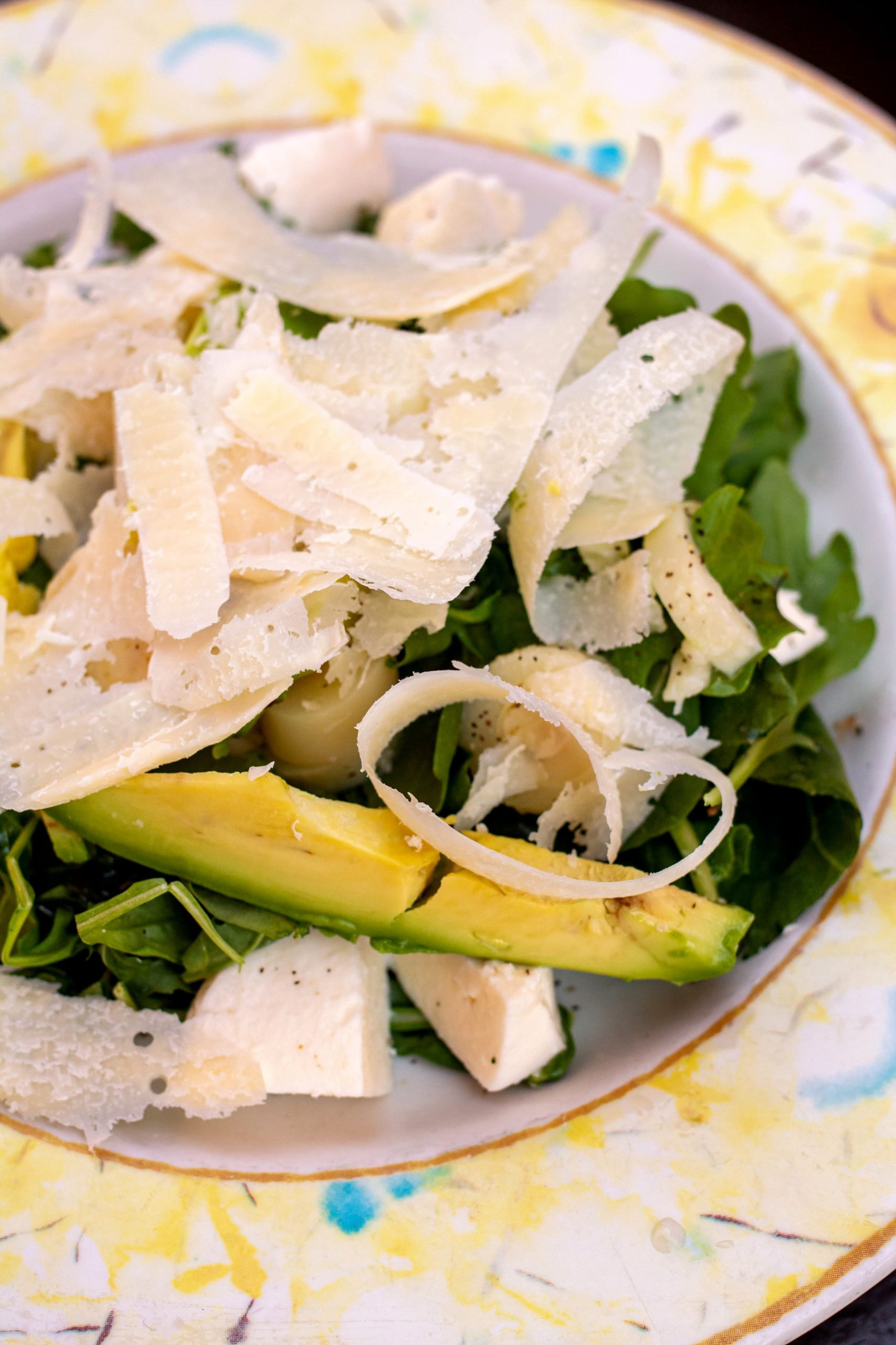 Arugula salad with sliced avocado, hearts of palm, and shredded cheese.