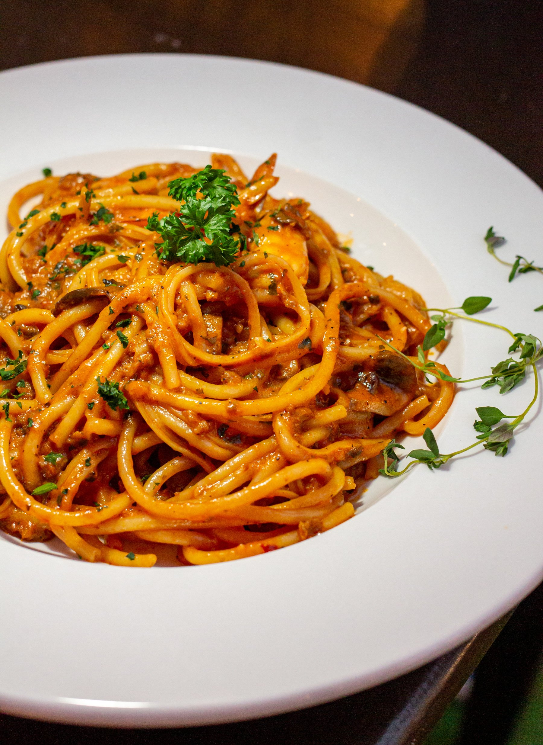 Pasta noodles in a red sauce with parsley on top.