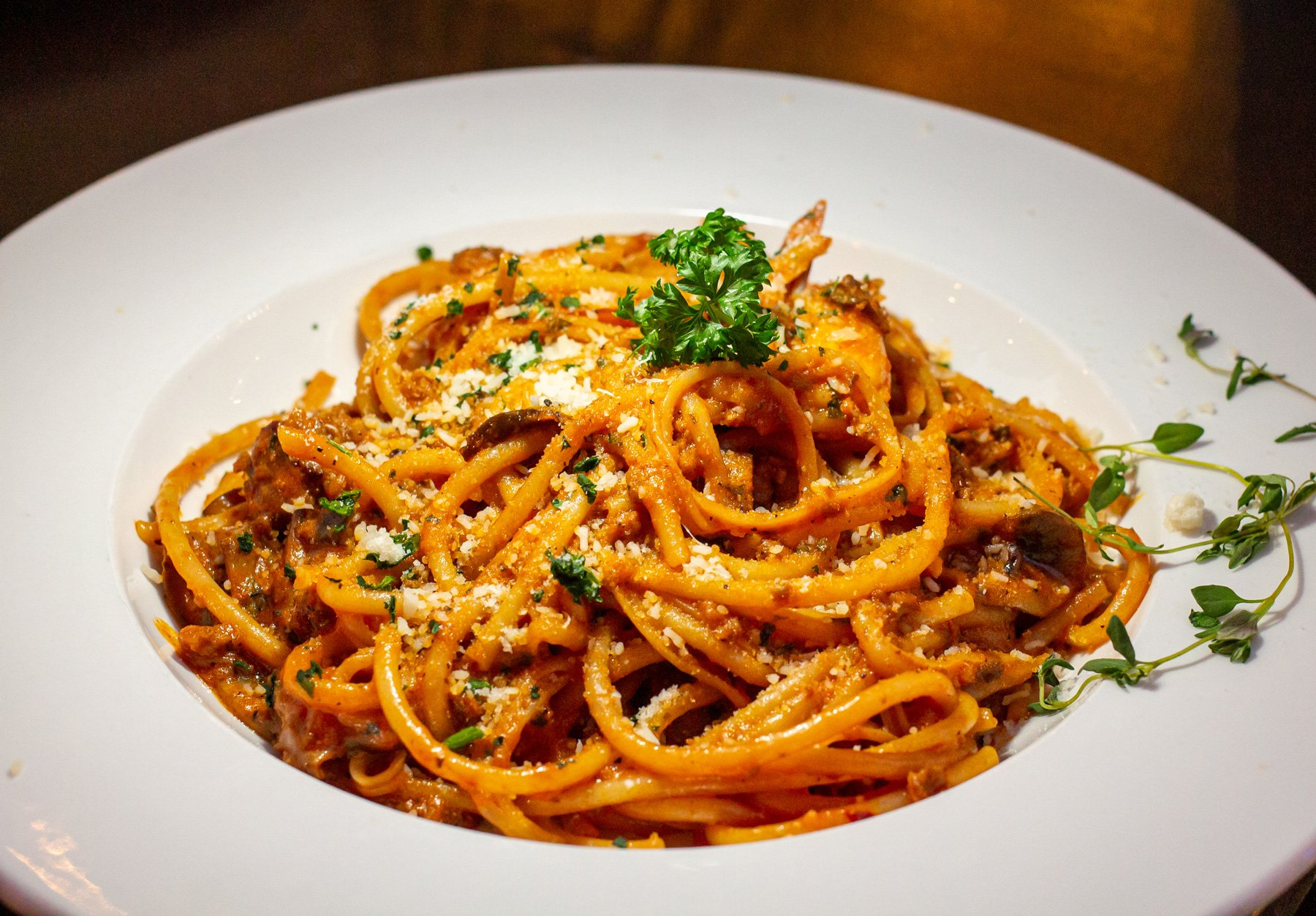 Pasta noodles in a red sauce with parsley on top on a white plate.