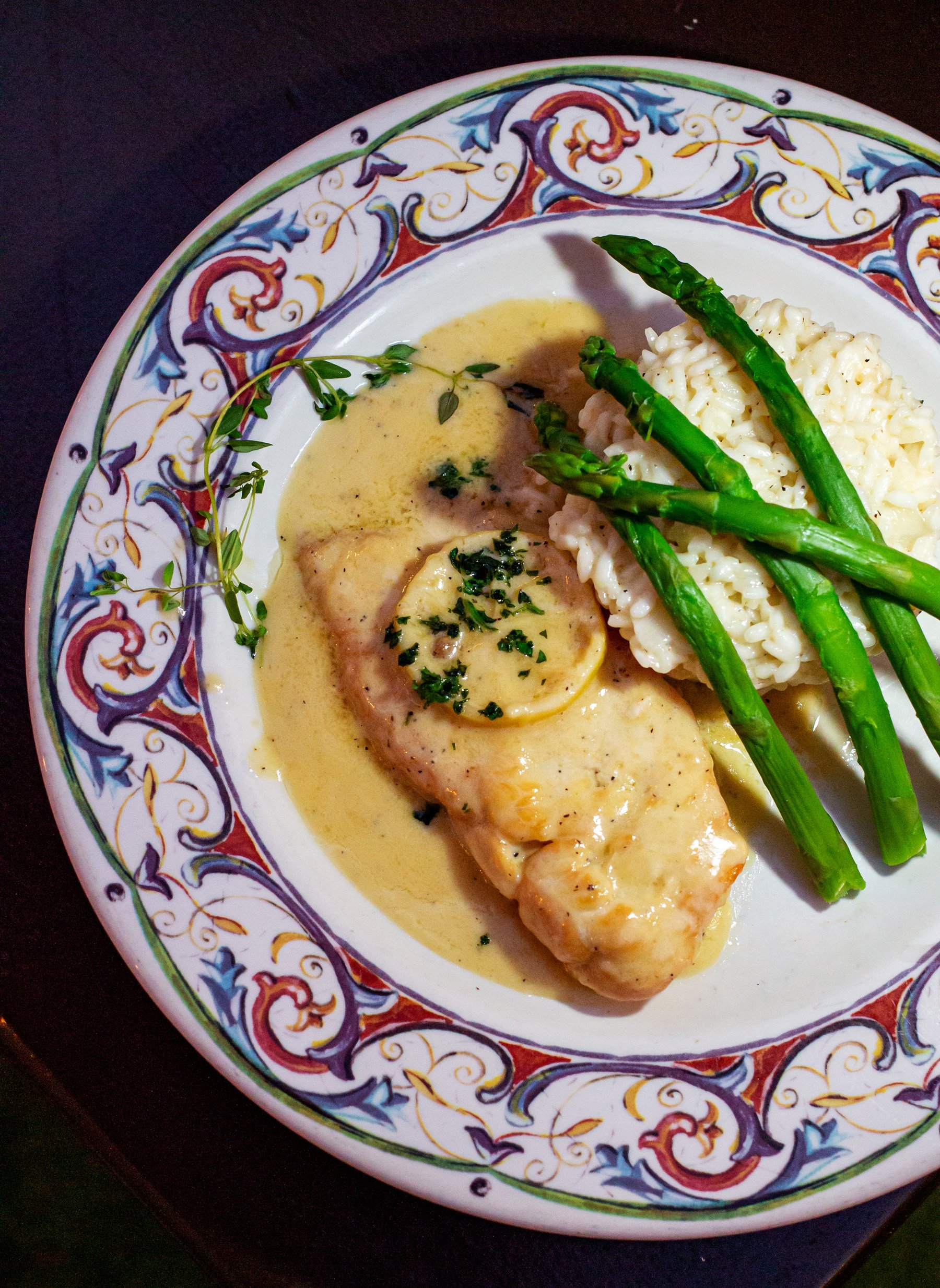 Lemon chicken with risotto and asparagus on a plate.