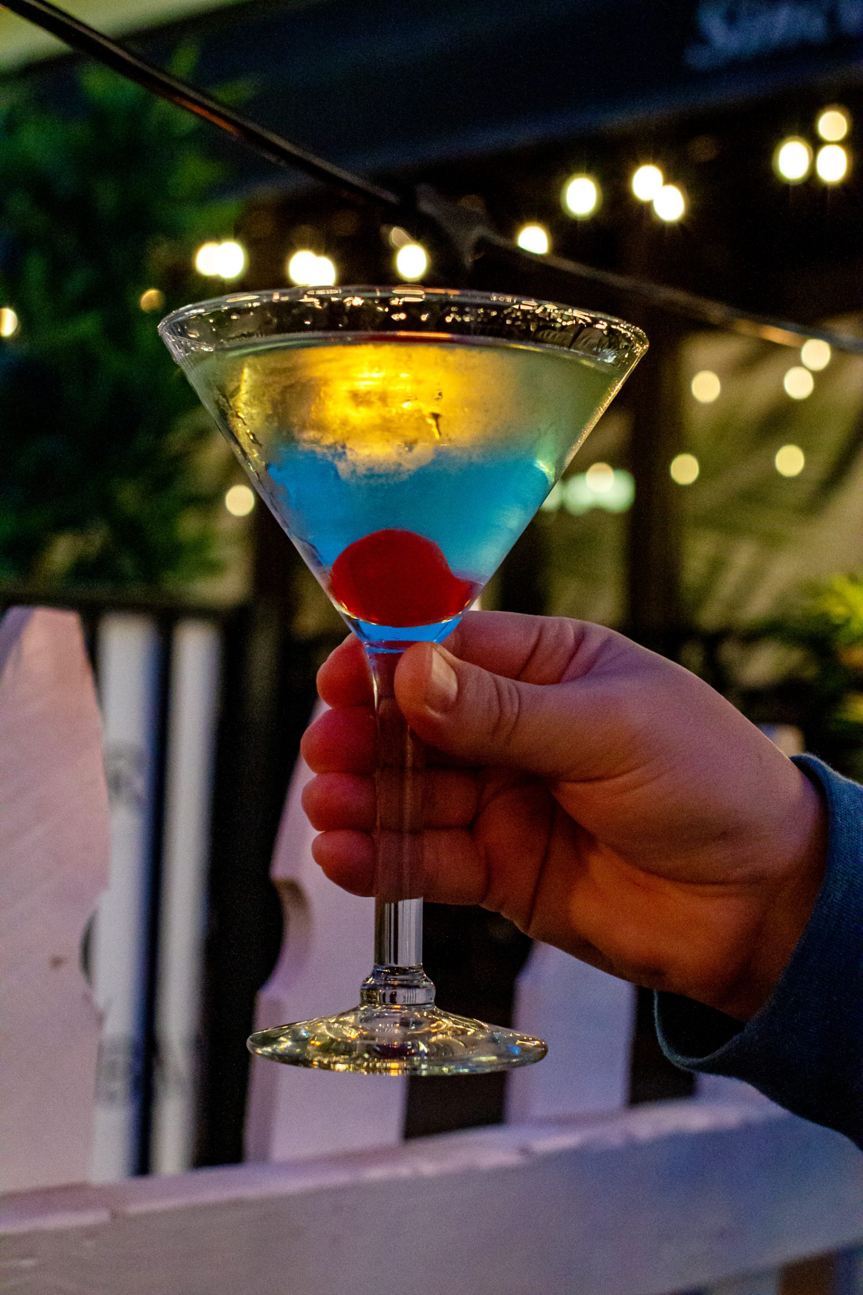 An apple martini being held up to decorative lights.