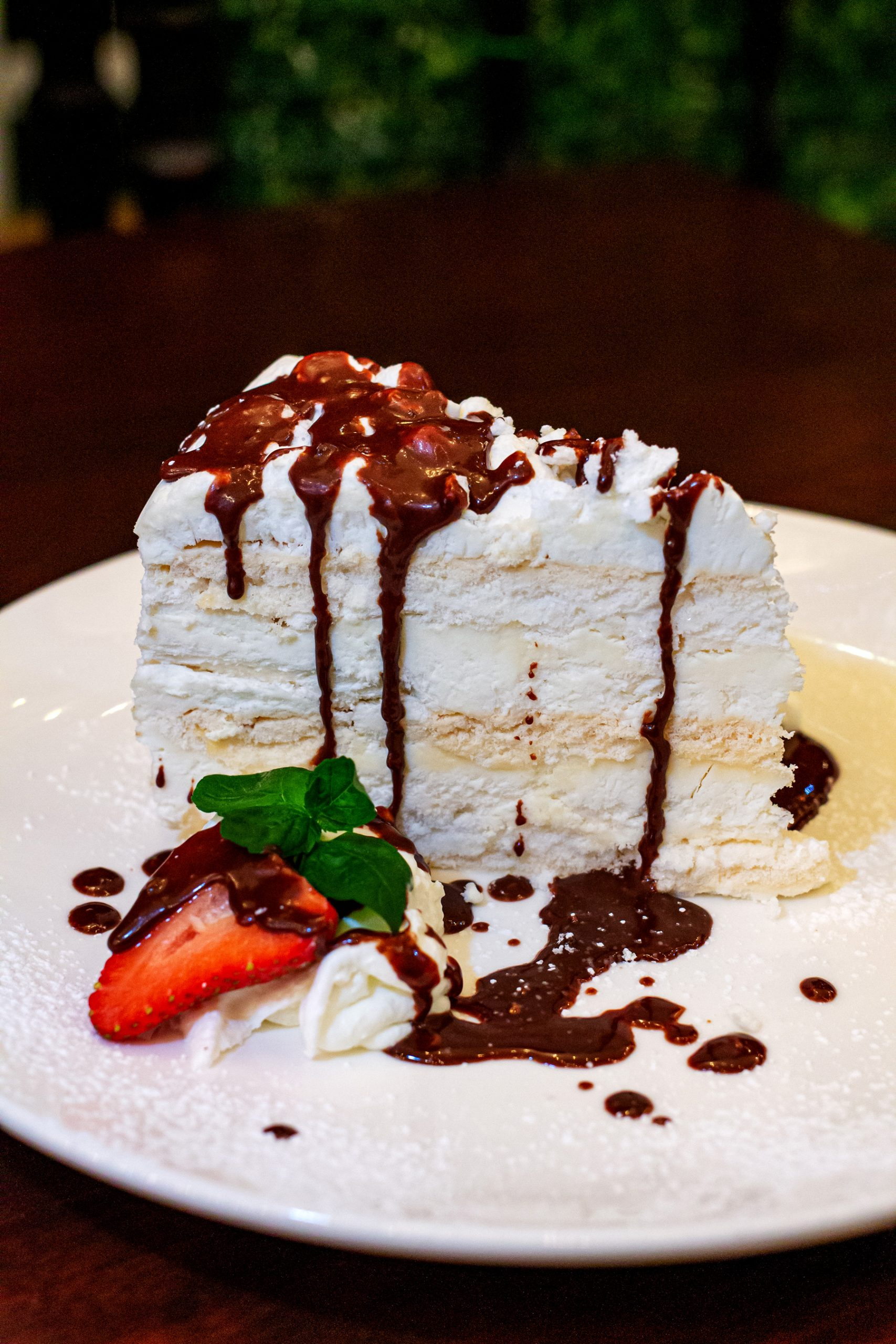 Meringue and vanilla ice cream cake drizzled with chocolate sauce on a white plate.