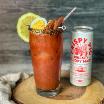 A tall glass of Crispy Pig with a lemon, egg and bacon garnish.