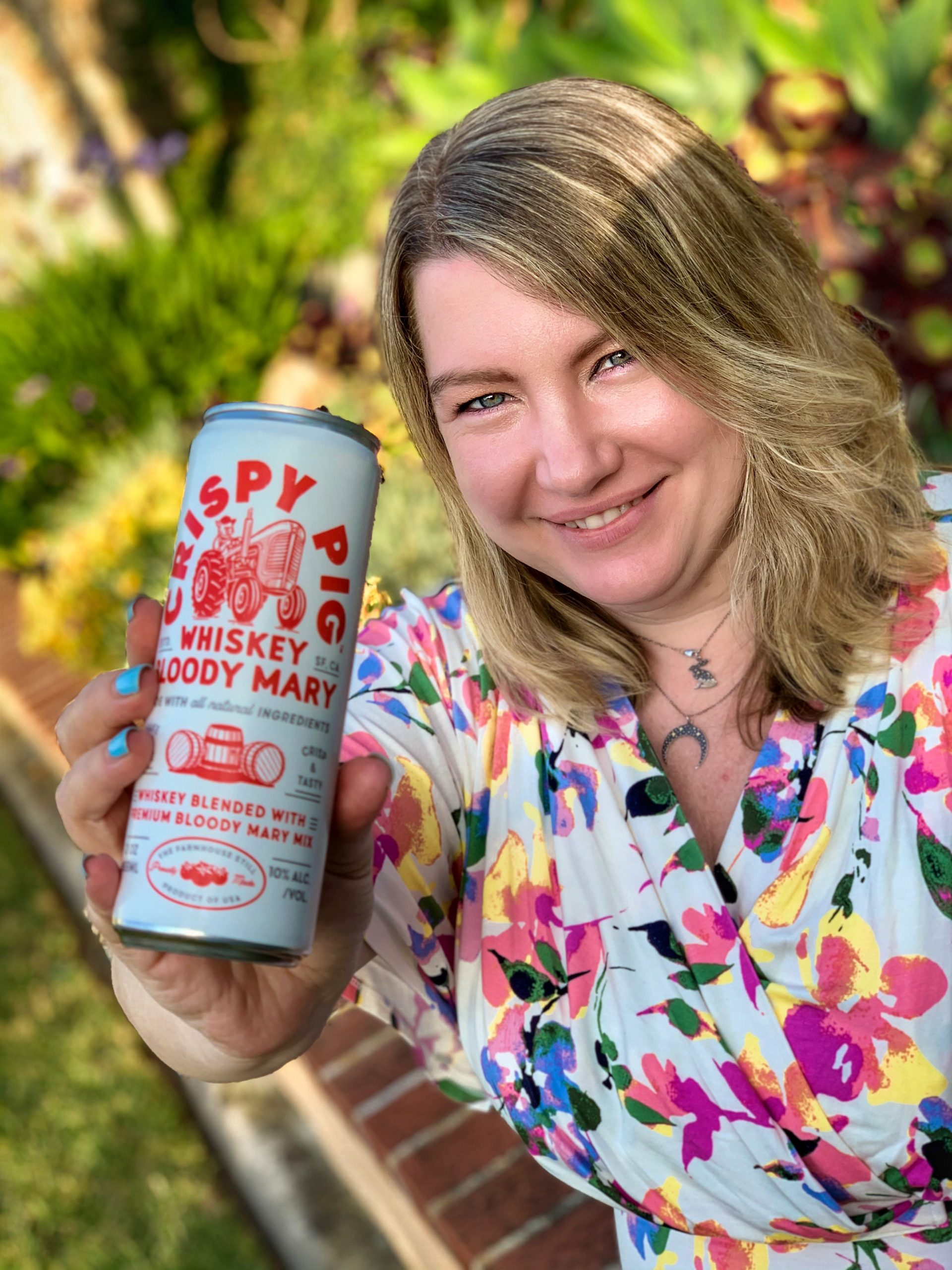 Natasha, smiling and holding a can of Crispy Pig
